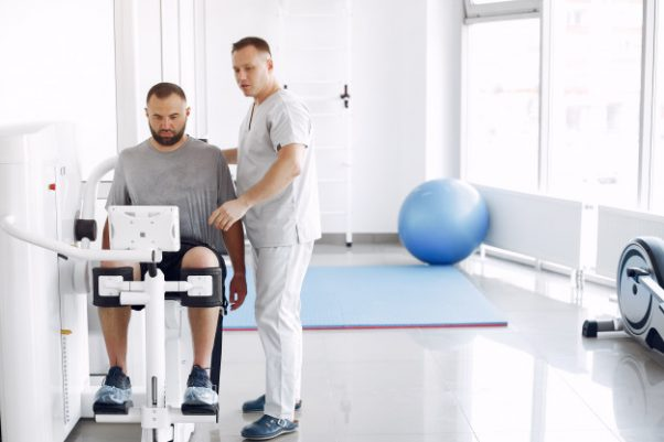 Doctor with a patient in physiotherapy clinic Free Photo